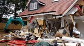 Un român a distrus 5 case noi, în Marea Britanie, cu un excavator